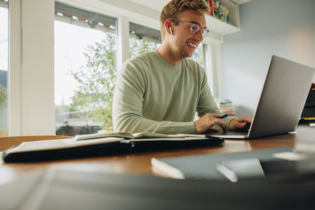 Smiling man working on laptop