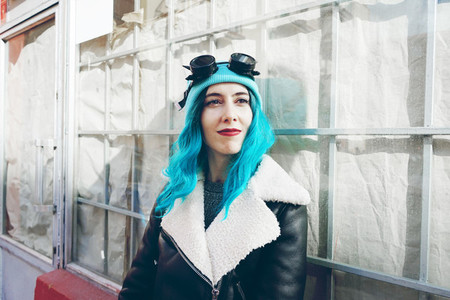Portrait of a punk or gothic young woman with blue colored hair