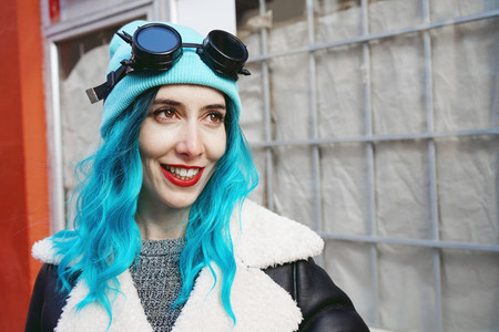Portrait of a punk or gothic young woman smiles with blue colore