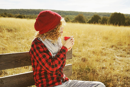 A young woman from behind in red plaid shirt with a wool cap and