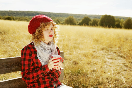 Front portrait of a young woman in red plaid shirt with a wool c