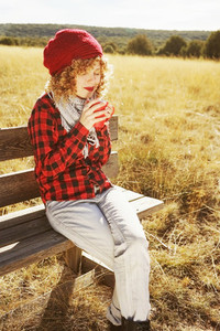 A young woman in red plaid shirt with a wool cap and scarf takin