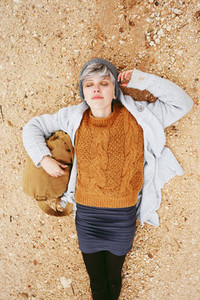 An adventurer young caucasian woman lying on grit ground beside