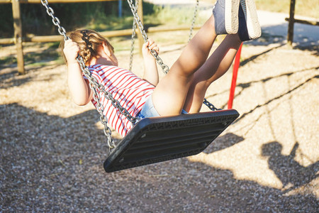 Young girl in a swing at the park