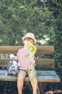 Little girl playing with a sunflower