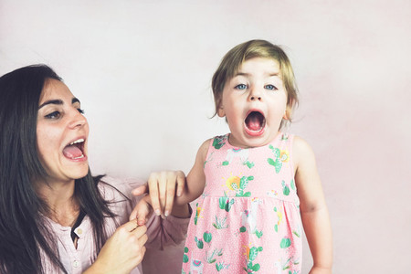Happy mom and baby girl in a studio photoshoot