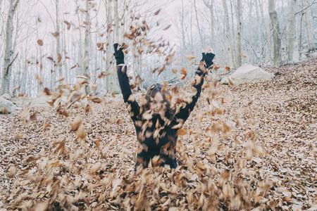 woman enjoying autumn leaves