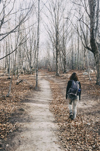 young woman relaxing walking through a forest in winter