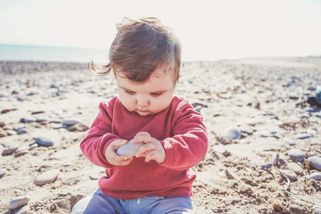 Little baby discovering the sand and sea