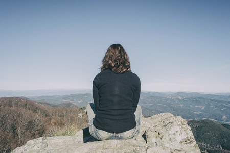girl from the back sitting on a top stone looking at the mountains