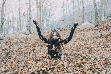 woman enjoying autumn leaves