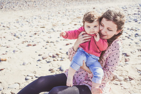 Happy family moment of a young mom enjoying a day on the beach w