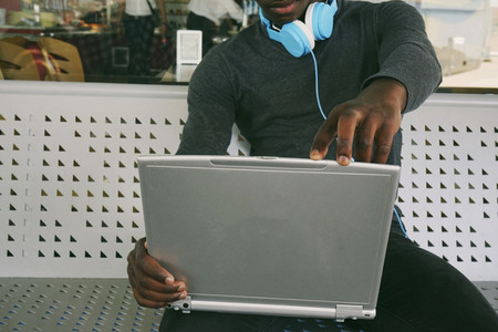 Close vision of a latptop and a young man using it