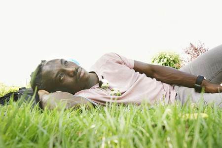 Young man daydreaming and lying on green grass