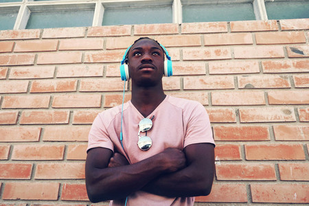 Young man leaning on brick wall wearing headphones
