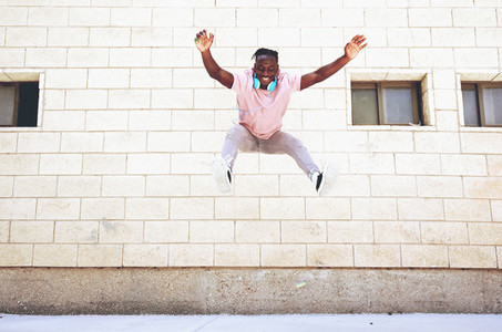 Young man jumping in the street wearing headphones