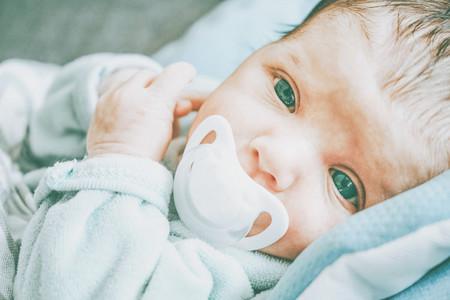 Newborn girl using a pacifier