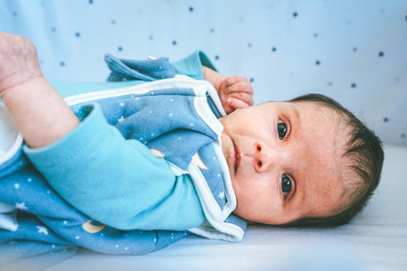 Lovely and curious newborn lying down in her little bed