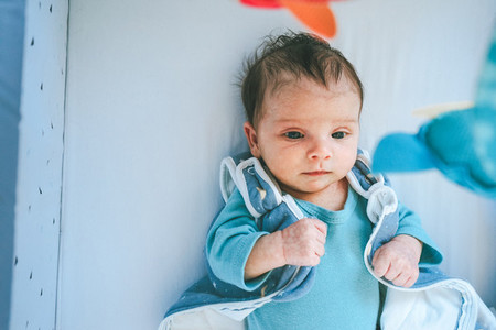 Lovely and playful newborn in her bedroom at home