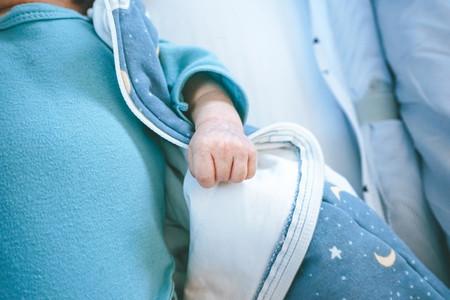 newborn little hand in a little cot