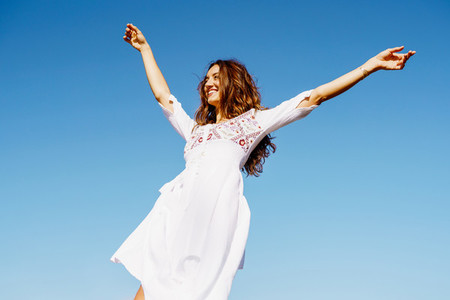 Young woman raising her arms in a beautiful white dress against a blue sky