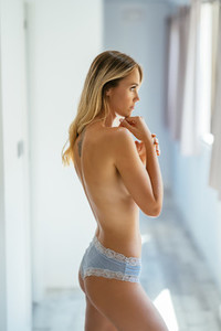 Beautiful slim topless woman wearing panties at home
