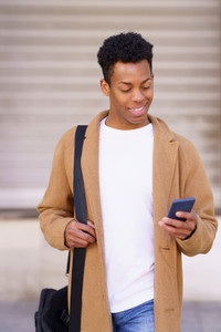 Smiling black man looking at his smartphone while walking down the street
