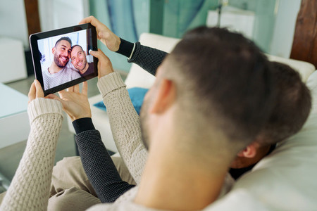 Gay couple making a selfie with a digital tablet sitting on the couch at home