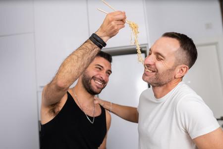 Man feeding pasta to his boyfriend in a fun way