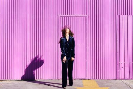 Woman wearing blue suit posing near pink shutter  moving her hair