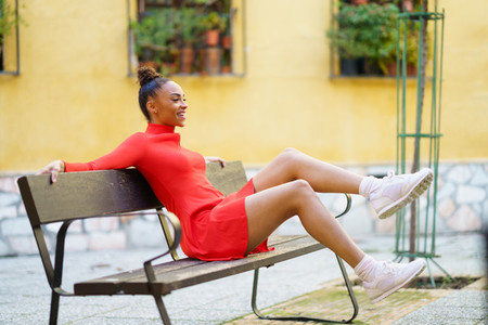 Happy mixed woman moving her legs in joy sitting on a bench in the street