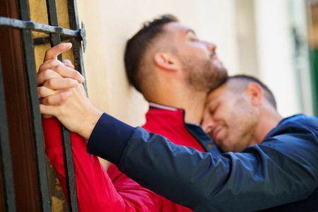 Gay couple hugging in a romantic moment outdoors