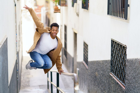 Young black man jumping for joy over a handrail in the street