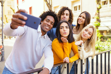 Multi ethnic group of friends taking a selfie outdoors with a smartphone