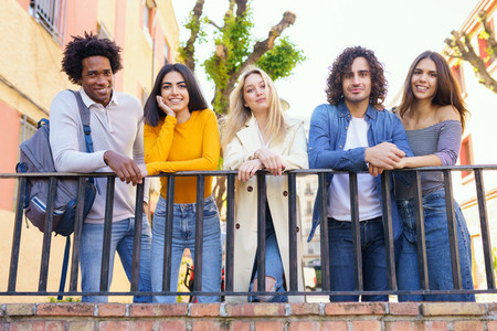 Multi ethnic group of friends gathered in the street leaning on a railing
