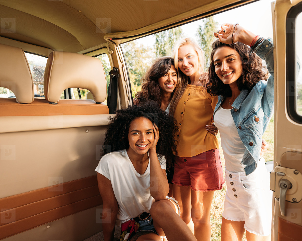 Multi ethnic group of female friends spending time together at camper van