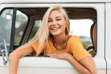 Happy female looking out of a window of van enjoying summer vacation
