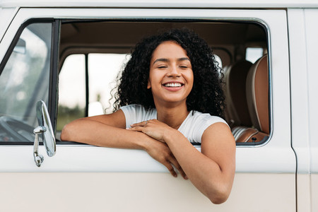 Cheerful brunette woman sitting on a driver seat in a camper van with closed eyes