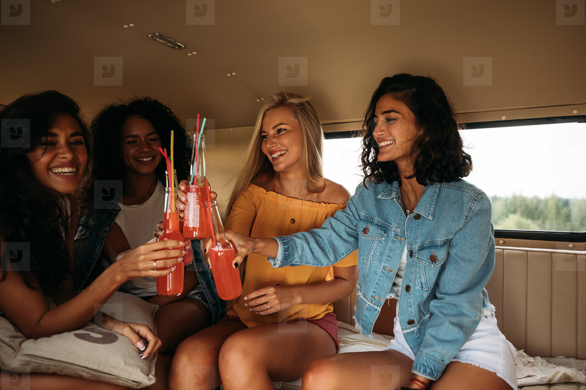 Group of diverse female friends celebrating vacation  Four women sitting with cocktails in a van