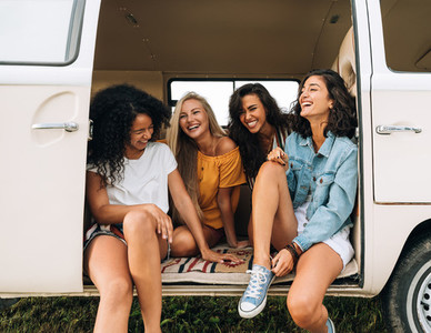 Multi ethnic group of women having fun while sitting in a car  Four friends traveling by car