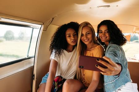 Group of female friends on a road trip taking selfie in a camper van