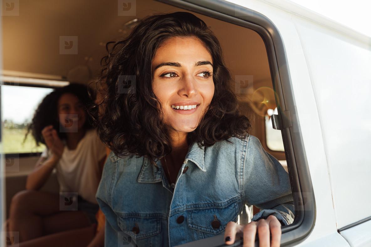 Beautiful brunette woman sitting in camper van looking out of window