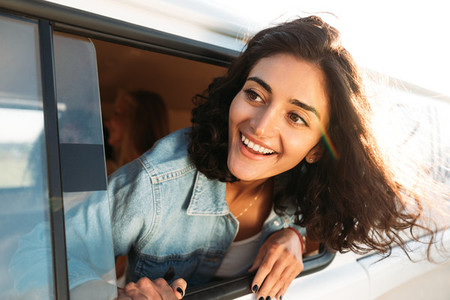 Young happy woman looks out of a camper van window enjoying a road trip