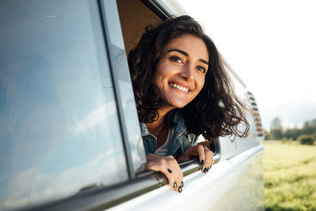 Beautiful brunette looks out of a window enjoying a road trip  Young woman in camper van looking into a distance