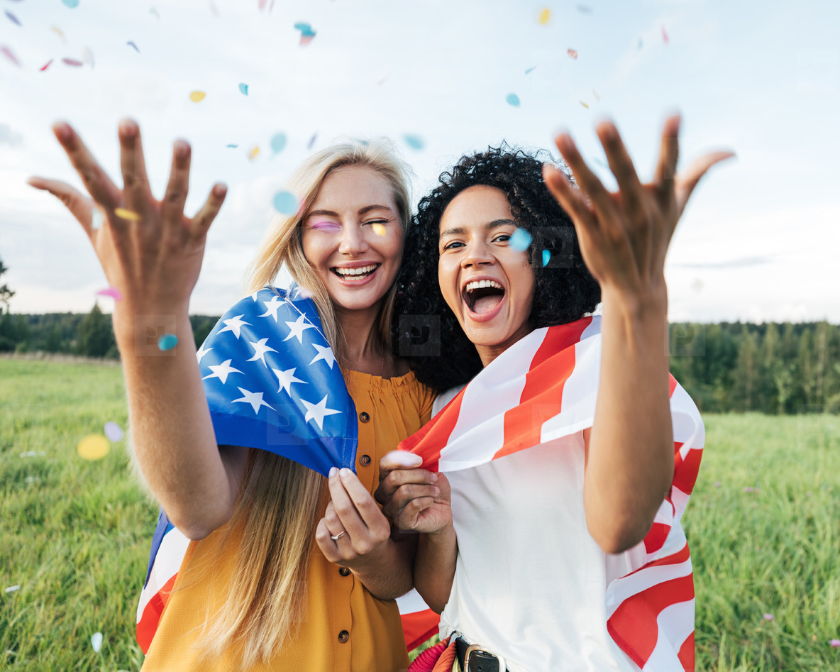 Two laughing female friends throwing confetti in the air while standing on a field with USA flag
