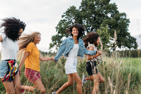 Group of a happy woman running and jumping outdoors  Female friends having fun on a field