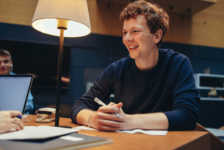 Cheerful male student studying in college library