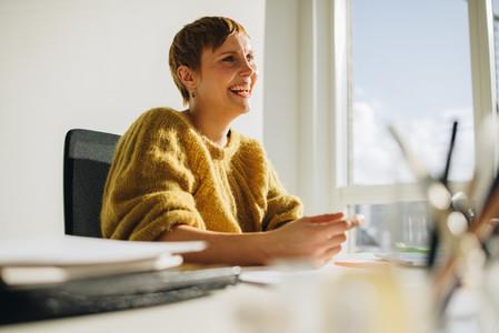 Happy female executive sitting at desk
