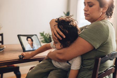 Woman with sick son having online consultation with family docto