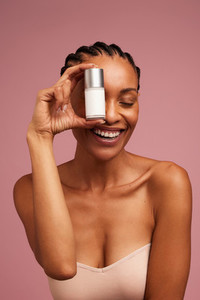 Woman with beautiful skin showing a beauty product